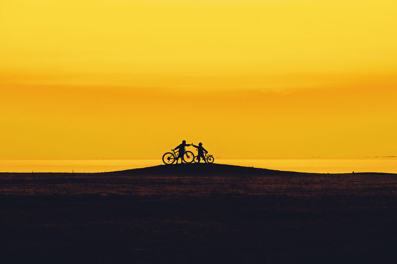 Silhouette friends riding bicycle on hill against orange sky