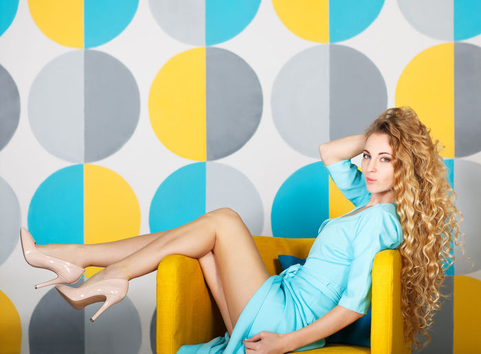 Young woman looking away while sitting on seat against wall