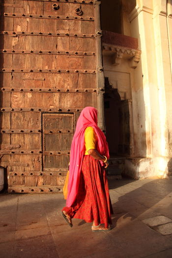 Side View Of Woman Walking By Wooden Door