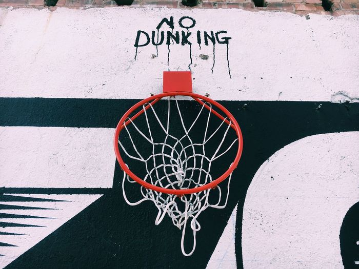 Low Angle View Of Basketball Hoop With Text On Wall