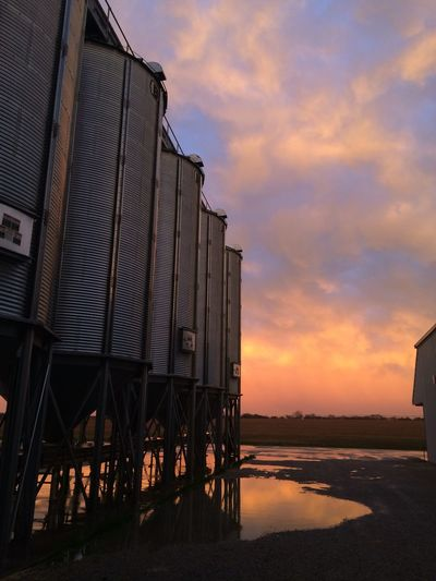 Low Angle View Of Cropped Silos Against Clouds