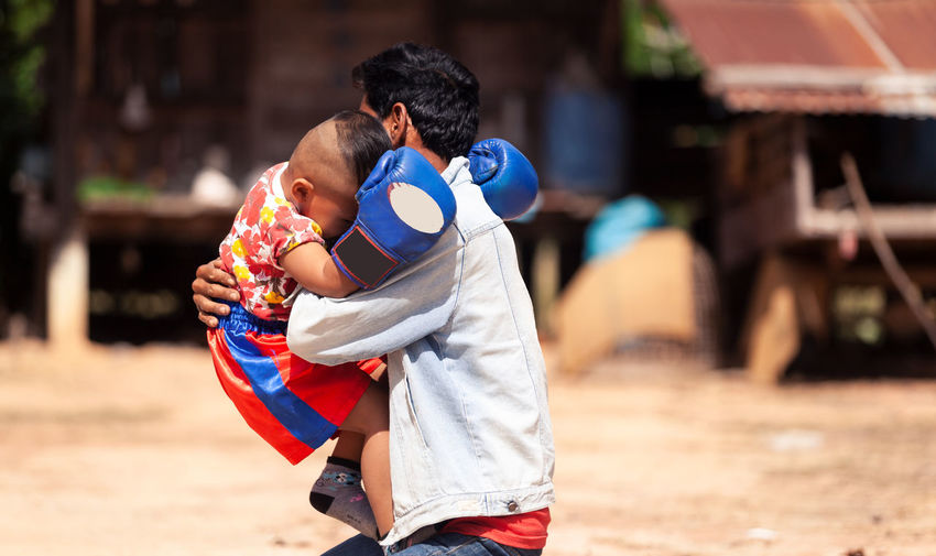 Men Togetherness Childhood Child Real People Males  Love Family Bonding Parent Family With One Child Focus On Foreground Adult Day Positive Emotion Emotion Lifestyles Women Innocence Son Outdoors Daughter Praying MuayThai Boxing