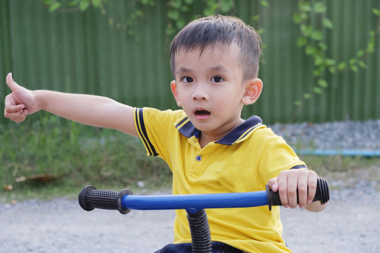 Portrait of cute boy showing thumbs up while riding bicycle on road