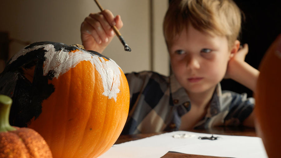Close-up of boy painting jack o lantern at home