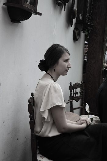Side view of thoughtful young woman sitting on chair at home