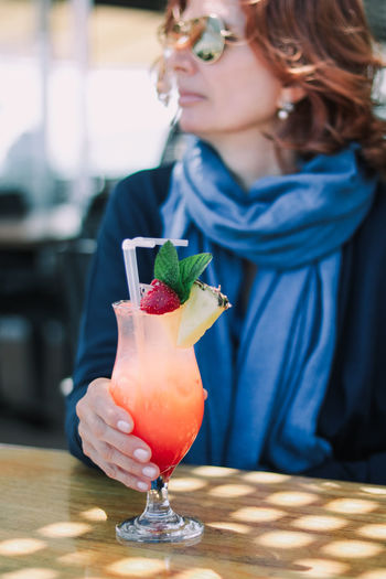 Midsection of woman holding drink on table