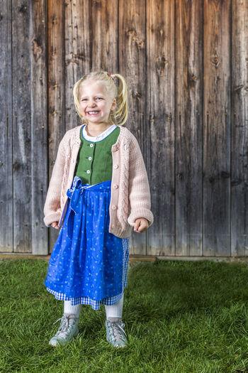 Portrait of happy girl standing on field