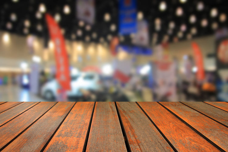 Wooden table and blurred image of motor show,show room,motor expo for background Abstract; Acceleration; Aerial; Auto; Automobile; Automotive; Background; Benz; Blur; Blurred; Bokeh; Business; Car; Color; Concept; Cooper; Crowd; Defocused; Depth; Distribution; Dream; Drive; Exhibition; Exterior; Inside; Interior; Lifestyle; Light; Min Close-up Day Focus On Foreground Indoors  No People Wood - Material
