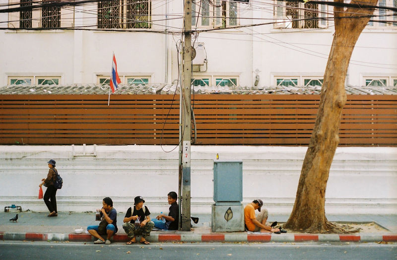 People sitting by building in city