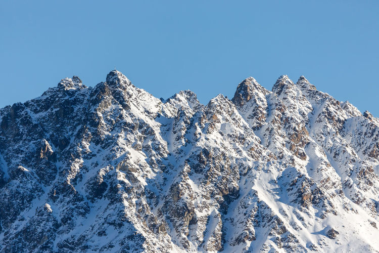 Low Angle View Of Snowcapped European Alps Against Clear Blue Sky