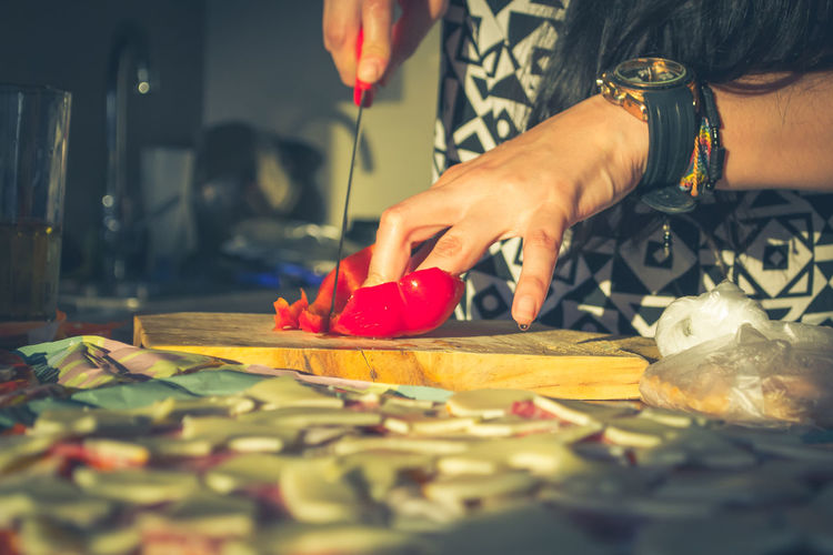 Midsection of woman cutting red bell pepper