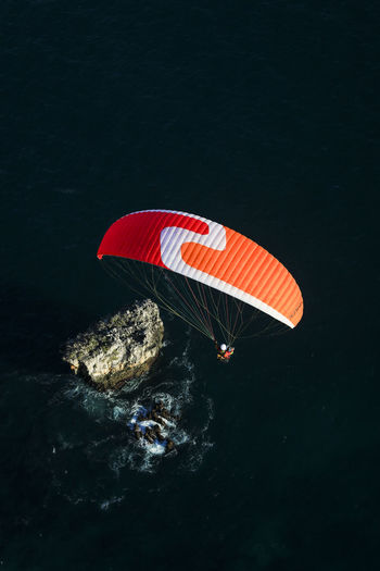 High angle view of red umbrella on rock by sea