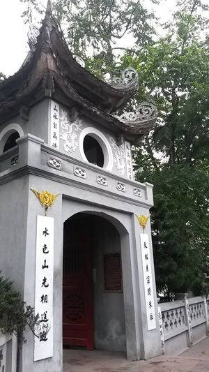 Vietnam Arch Architecture Belief Building Building Exterior Built Structure Communication Day Entrance Hanoi Low Angle View Nature No People Non-western Script Ornate Outdoors Place Of Worship Plant Religion Script Spirituality Temple Text Tree