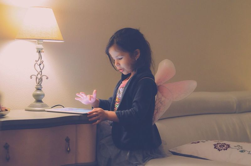 Girl wearing fairy wings using digital tablet while sitting on sofa by illuminated lamp shade
