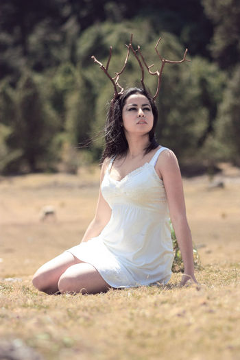 Beautiful woman wearing artificial horn while sitting on field