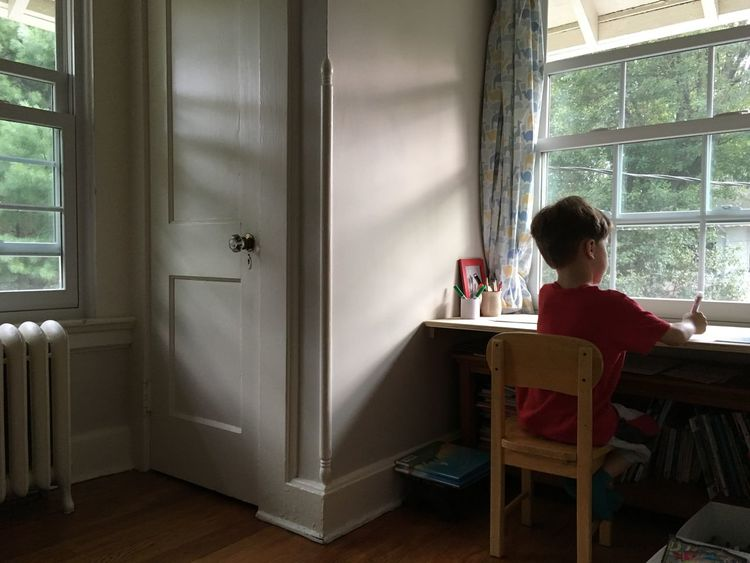 Boy Casual Clothing Contemplation Day Domestic Room Drawing Full Length Homework Kid Leisure Activity Lifestyles Playing Relaxation Sitting Sitting On Table Sitting On Window Window Windows Writing
