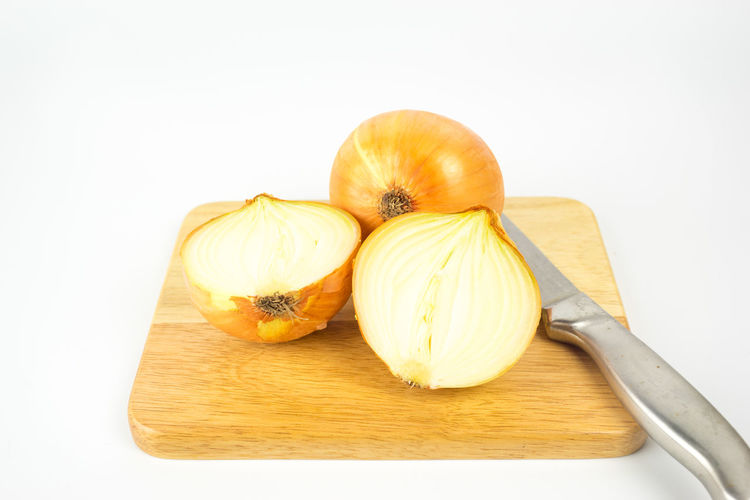 Close-up of bread on cutting board against white background