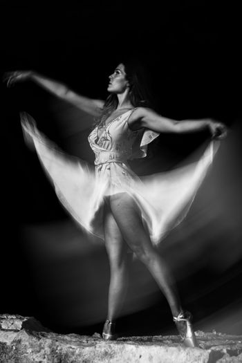 Midsection of woman dancing against black background