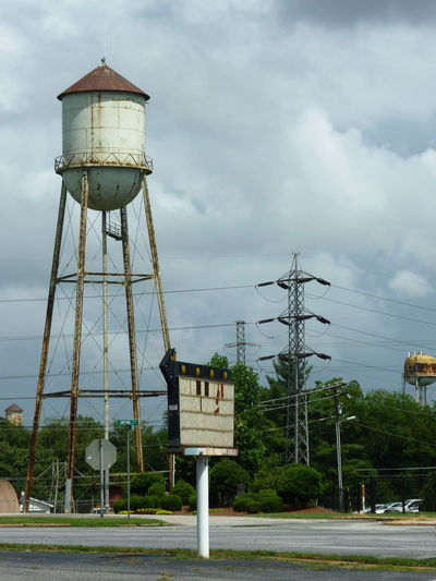 Water tower by building against sky