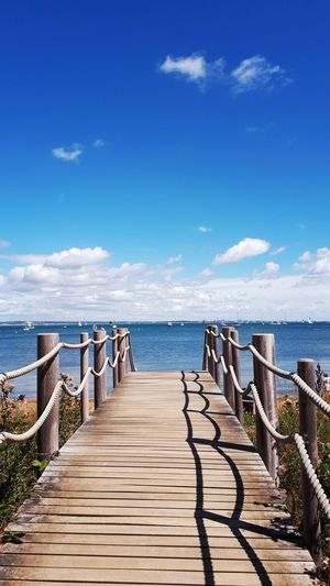 Wooden footpath leading to sea against sky