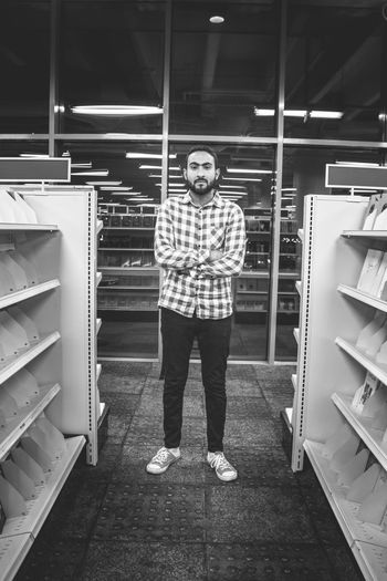 Portrait of young man standing amidst shelves in store