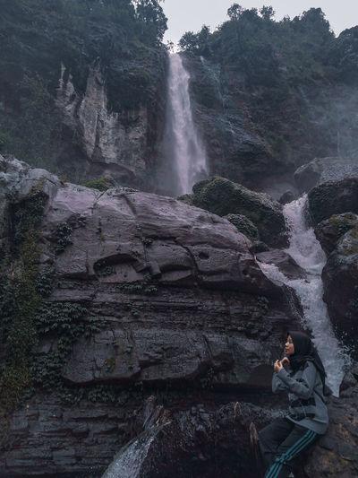 Man surfing on rocks against waterfall