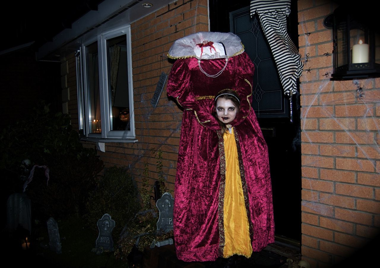 Portrait of woman in halloween costume standing outside house at night