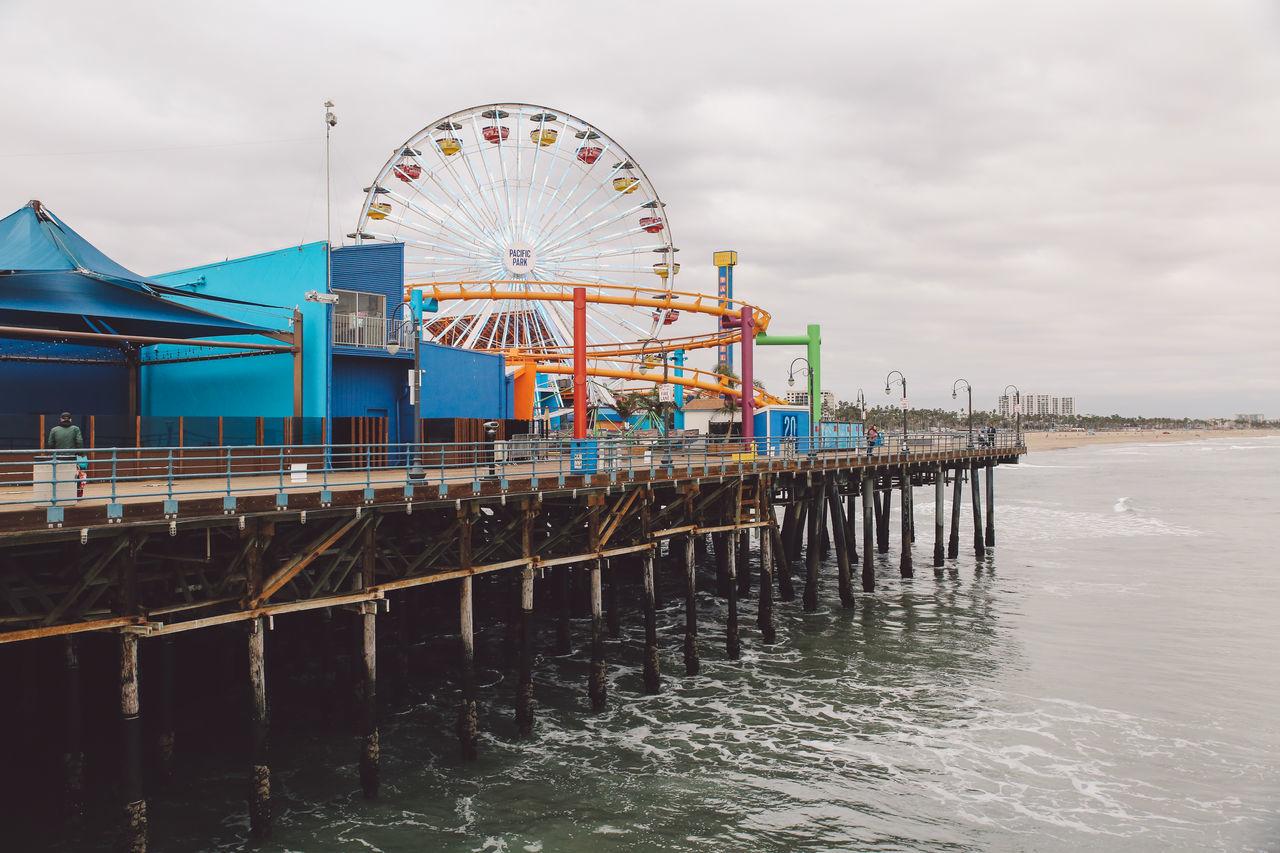 amusement park, arts culture and entertainment, water, sky, ferris wheel, sea, cloud - sky, amusement park ride, beach, built structure, outdoors, no people, day, nature, architecture