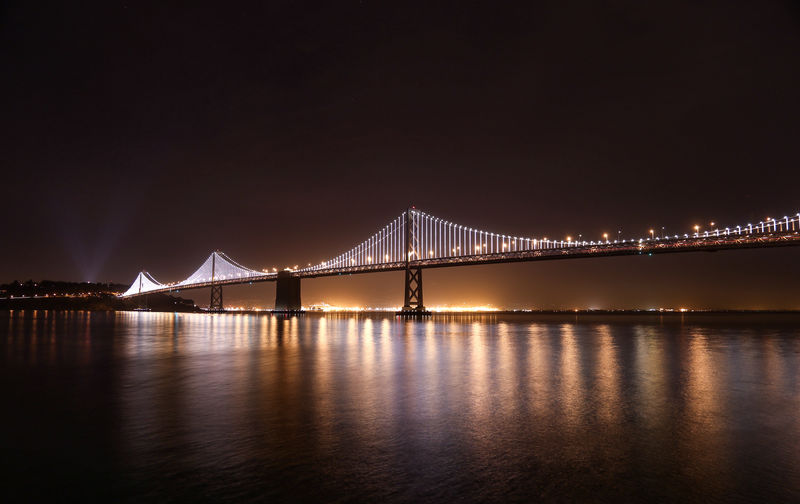 Illuminated Oakland Bay Bridge Over Sea Against Clear Sky At Night