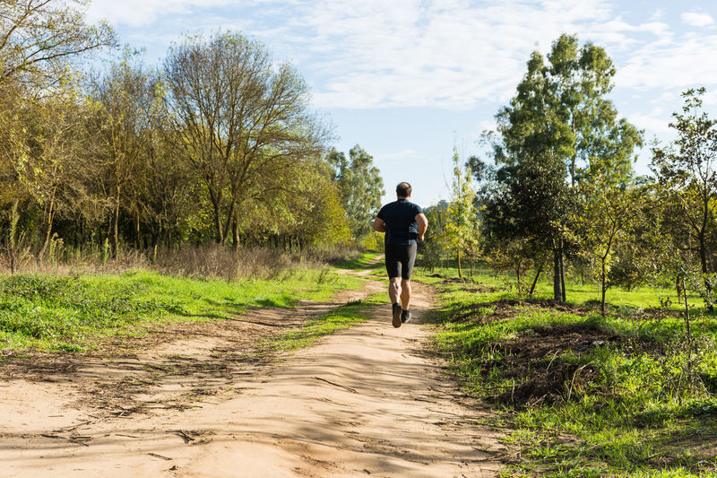 Rear view of man running on footpath against sky