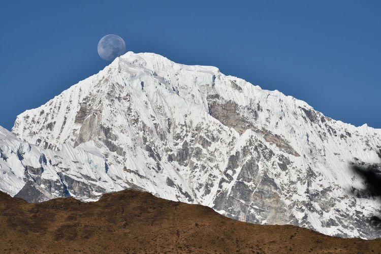 Scenic view of the moon behind snowy mountains