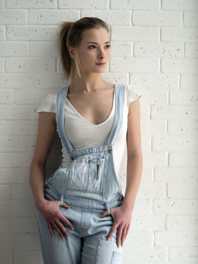 beauty young caucasian woman in blue denim overalls and a white T-shirt front of brick wall Adult Adults Only Beauty Blue Brick Caucasian Day Denim Indoors  Looking At Camera One Person One Woman Only One Young Woman Only Only Women Overalls People Portrait Standing Waist Up Wall White Woman Young Young Adult Young Women