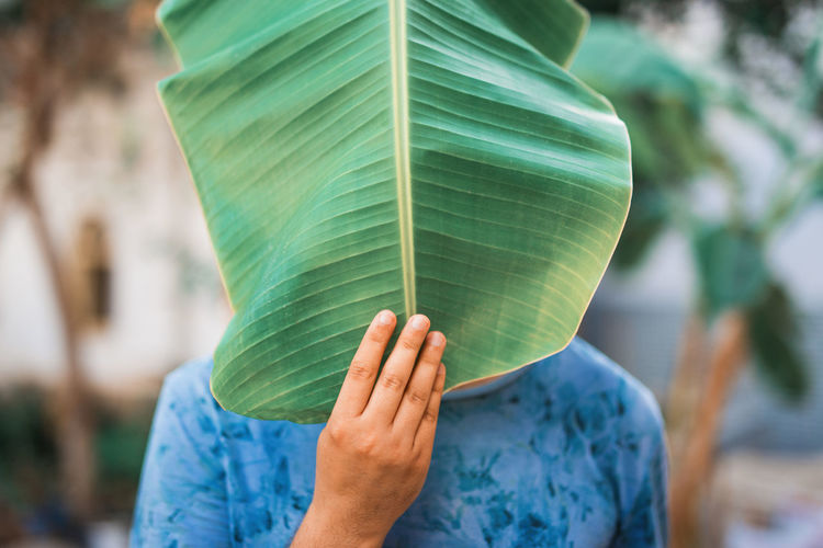 Midsection of person holding banana leaf over face