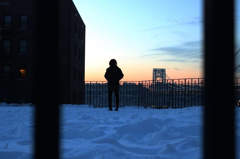 Full length of silhouette person standing against george washington bridge during winter