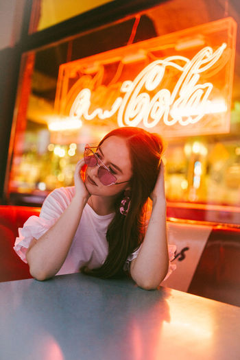 Portrait of young woman sitting on table in restaurant