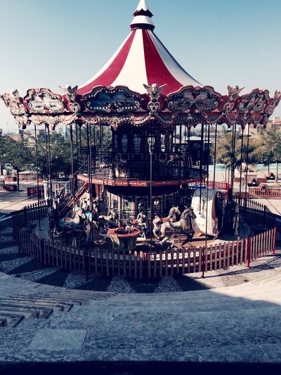Carousel in amusement park against clear sky
