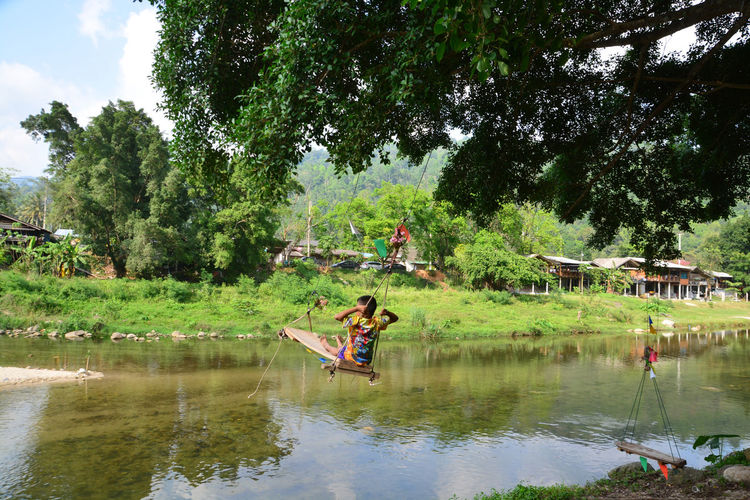 People in boat on lake against trees