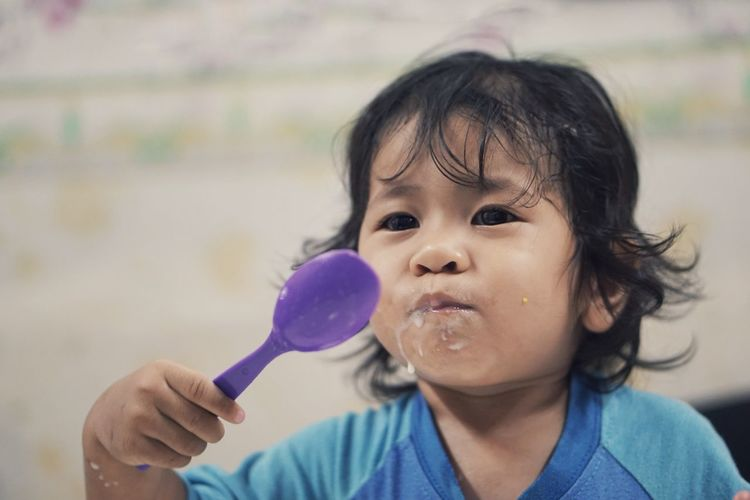 Close-up of cute girl eating food while holding spoon
