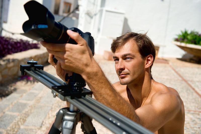 Shirtless man photographing through camera