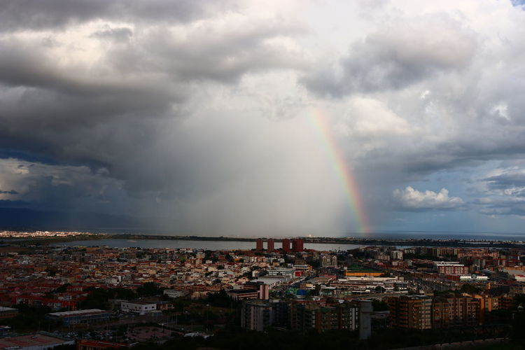 Aerial view of rainbow over buildings in city against sky