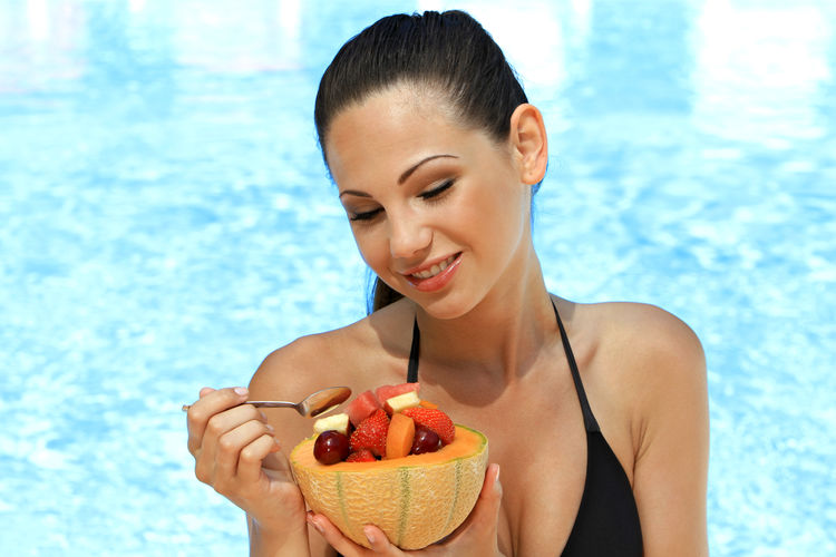 Smiling beautiful young woman having fruits against swimming pool