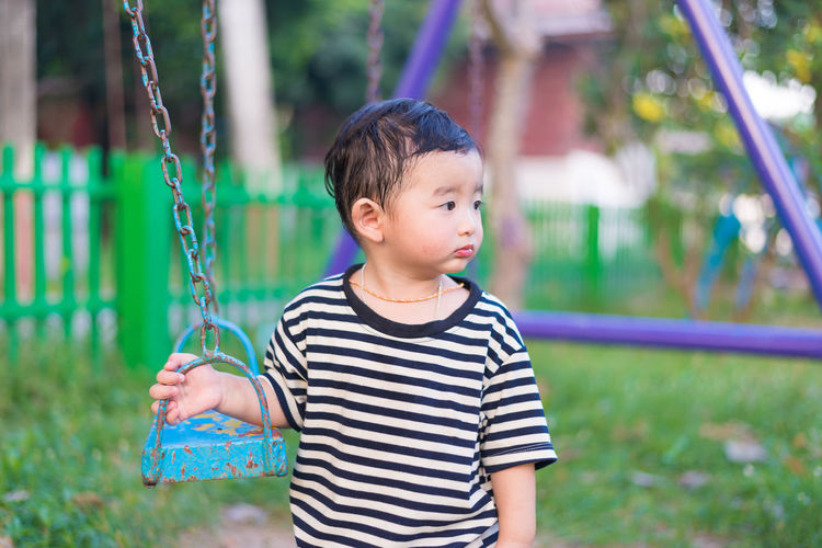 Boy holding swing at park