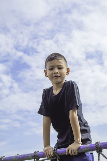 Portrait of boy standing by railing against sky