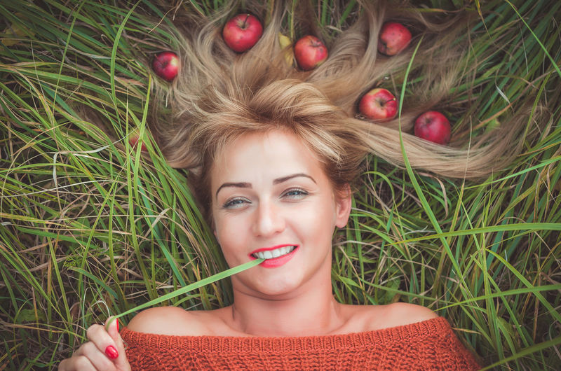 Woman laying on green grass with loose hair with apples Hairstyle Hair Lying On Back Young Women Fruit Front View Beauty Freshness Looking At Camera Food And Drink Food Headshot Women Grass Lying Down Beautiful Woman Young Adult Plant One Person Portrait Leisure Activity Real People Lifestyles Green Color