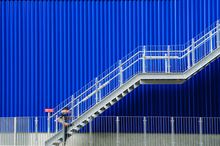 Ascending stairs of rising staircase going upward,railing Architecture Blue Bridge Bridge - Man Made Structure Building Exterior Built Structure City Connection Corrugated Industry Metal Modern Nature No People Outdoors Pattern Railing Sky Staircase Steel Transportation Wall - Building Feature