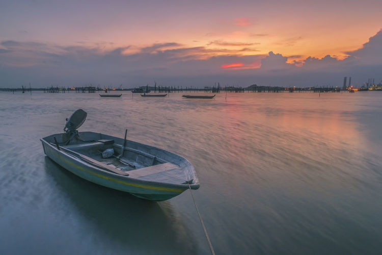 Boat moored at beach against sky during sunset