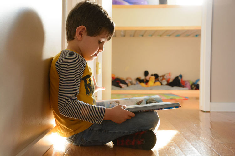 Side view of boy reading book while sitting on floor at home