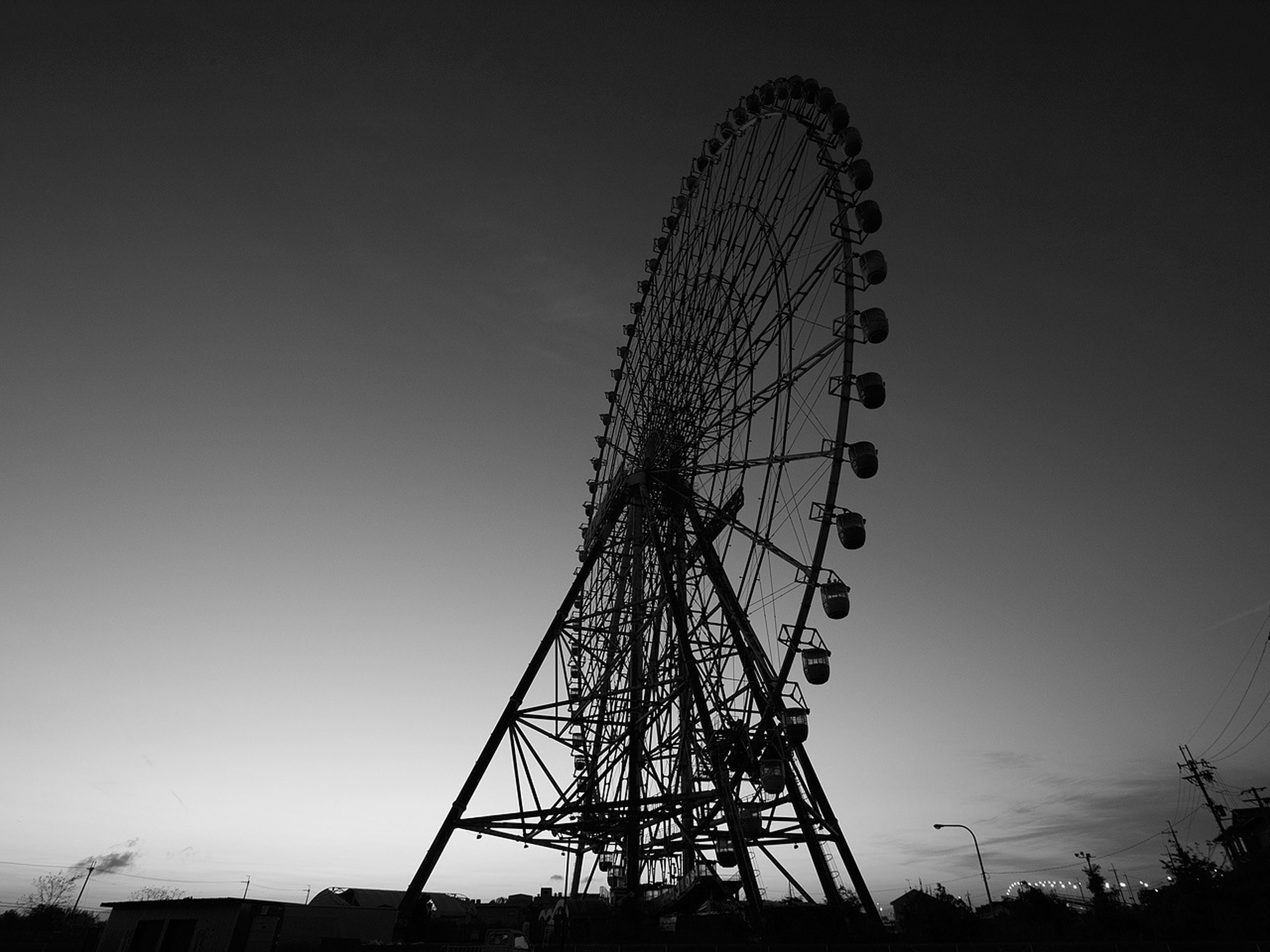 low angle view, ferris wheel, amusement park, amusement park ride, arts culture and entertainment, clear sky, built structure, sky, silhouette, architecture, tall - high, outdoors, dusk, copy space, fun, large, tower, enjoyment, big wheel, no people