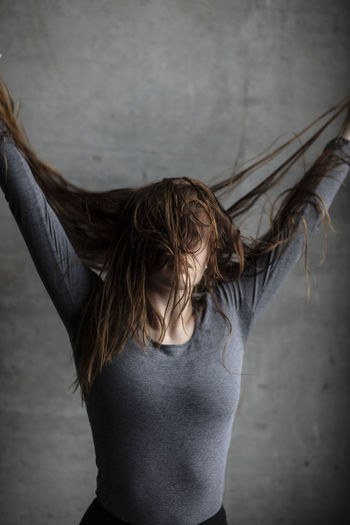 Young woman pulling her hair upwards Extreme Front Facing Hairplay Looking Away Standing Arms Raised Beauty Brunette Casual Clothing Female Beauty Front View Grey Color Grey Wall Hair Hairstyle Human Hair Indoors  Long Hair Model Obscured Face One Person Portrait Portrait Photography Waist Up Wild