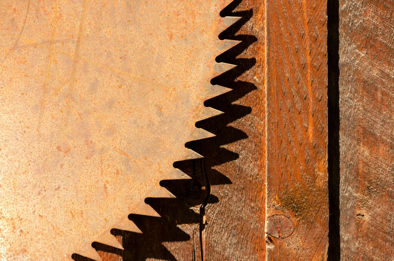 Close-Up Of Rusty Circular Saw Against Wood